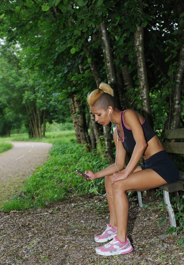 Vila och lyssnande musik för kvinna, når att ha gjort sportar utomhus royaltyfria bilder