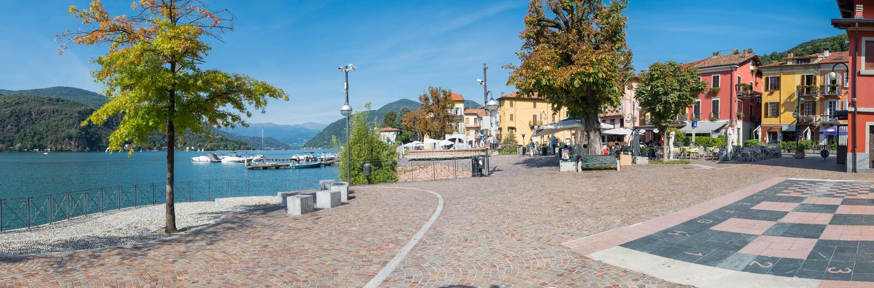 Vila pitoresca, passeio do lago e centro histórico, com restaurantes e barras, em Porto Ceresio, lago Lugano, Itália foto de stock royalty free
