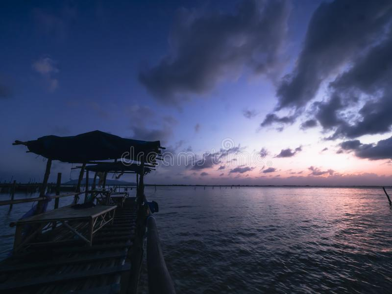 Vila punkt i havet för fisherman med solnedgång och härlig himmel arkivfoton