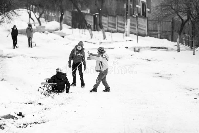 Vila romena do sul pequena Cenas de um inverno temperamental com as crianças que jogam com pequenos trenós e que apreciam a neve fotografia de stock royalty free