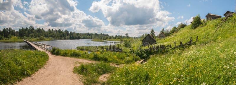 Vila russian norte Dia de verão, rio, casas de campo velhas na costa foto de stock