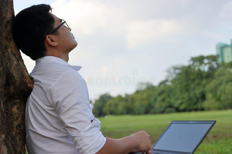 Vila tid Asiatisk ung man som ser himlen efter arbete mot hans bärbar dator royaltyfri fotografi