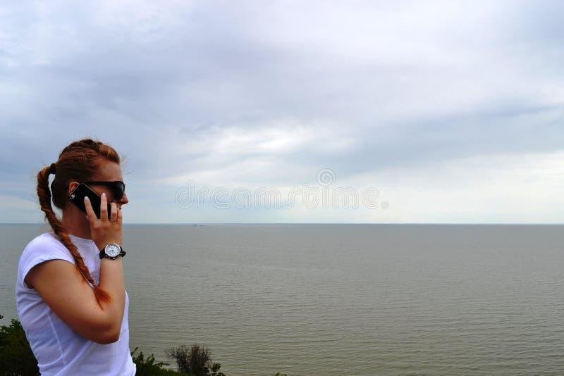 vila Utomhus- stående av en härlig lycklig brunettkvinna i solglasögon och hatt som talar på hennes mobiltelefon på havsbakgrund royaltyfria bilder