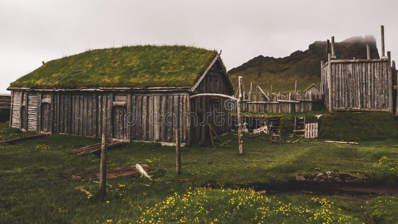 Vila velha de viquingue em Islândia com monte nevoento construções de madeira velhas cobertas na grama fotos de stock