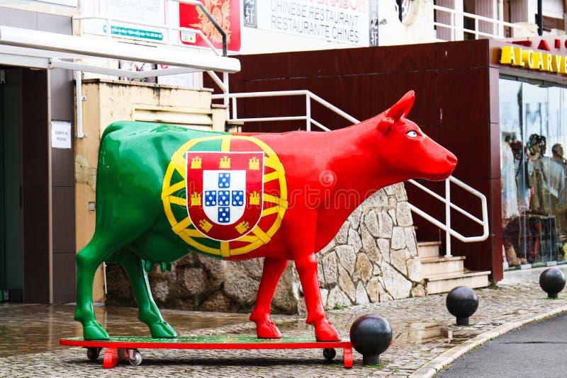 Vilamoura, Portugal - uma vaca pintada com a bandeira portuguesa está na frente de uma loja de lembrança perto do cais foto de stock royalty free