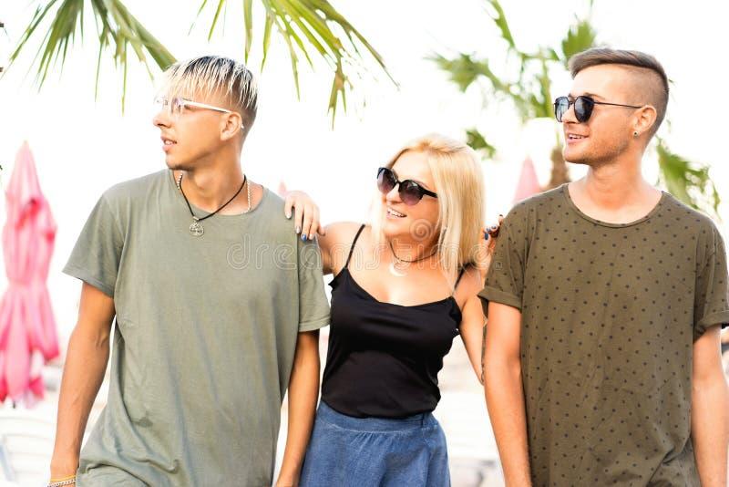 Vilar det gladlynta företaget för tre vänner på en tropisk strand och drin royaltyfri fotografi