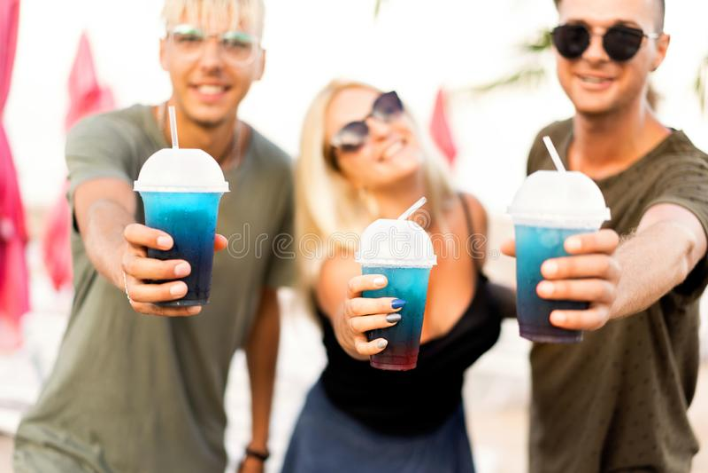 Vilar det gladlynta företaget för tre vänner på en tropisk strand och drin royaltyfria foton