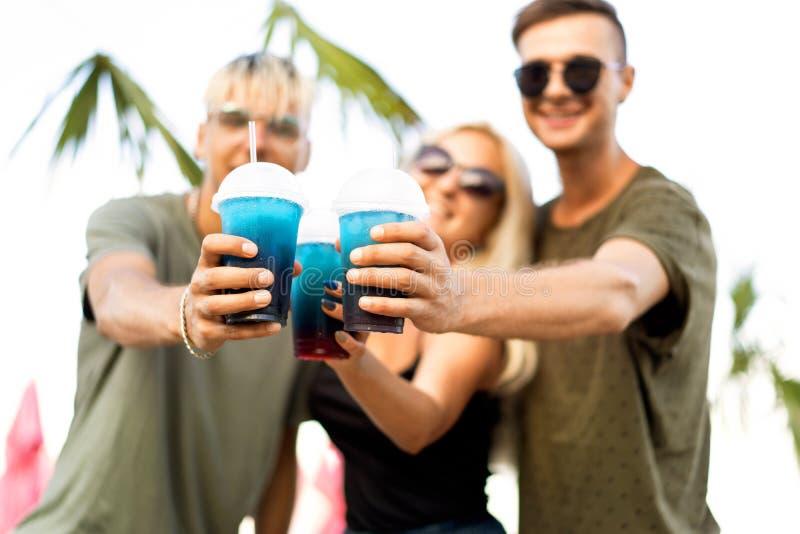 Vilar det gladlynta företaget för tre vänner på en tropisk strand och drin royaltyfri bild