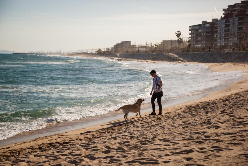 VILASSAR DE MAR, ESPANHA, 13 de maio de 2019: Mulher levando seu cachorro para passear em uma praia perto de Barcelona fotografia de stock