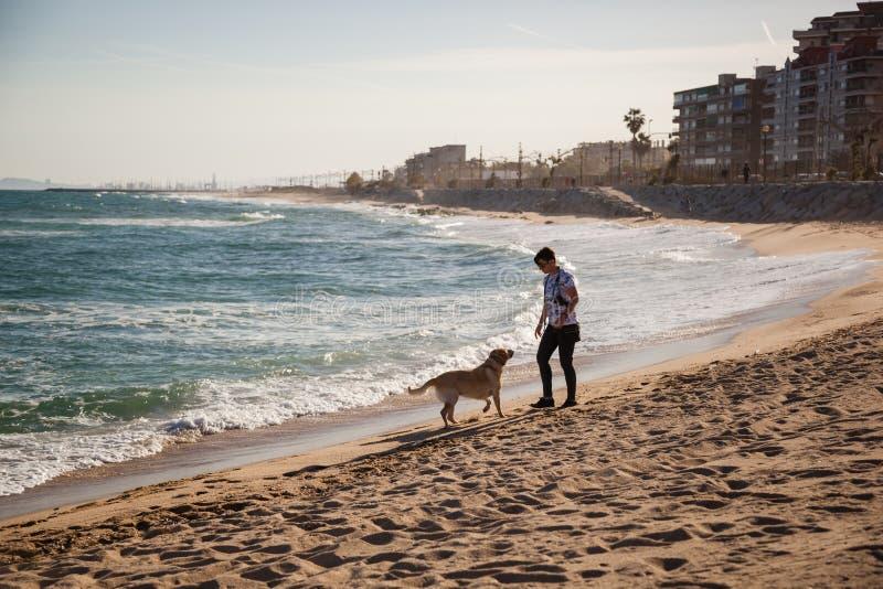 VILASSAR DE MAR, SPANIEN 13 maj 2019: Kvinnor som tar sin hund för en promenad på en strand nära Barcelona arkivbild