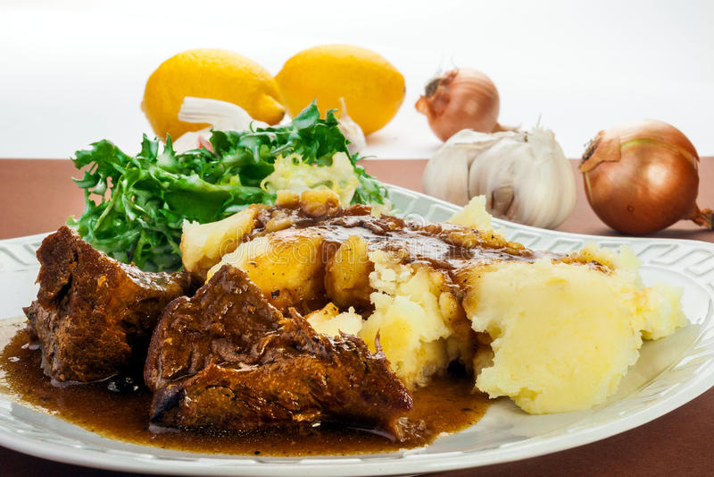 Vildsvinköttsås med potatisar arkivbild