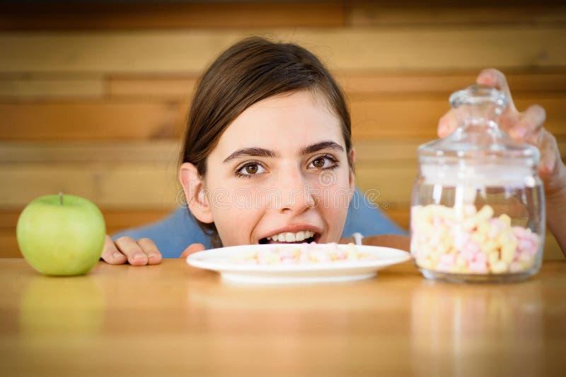 Vilka bättre smaker Sött och sjukligt eller organiskt och naturligt Kvinnan väljer vilken mat som ska ätas Nätt kvinnablick på arkivbild