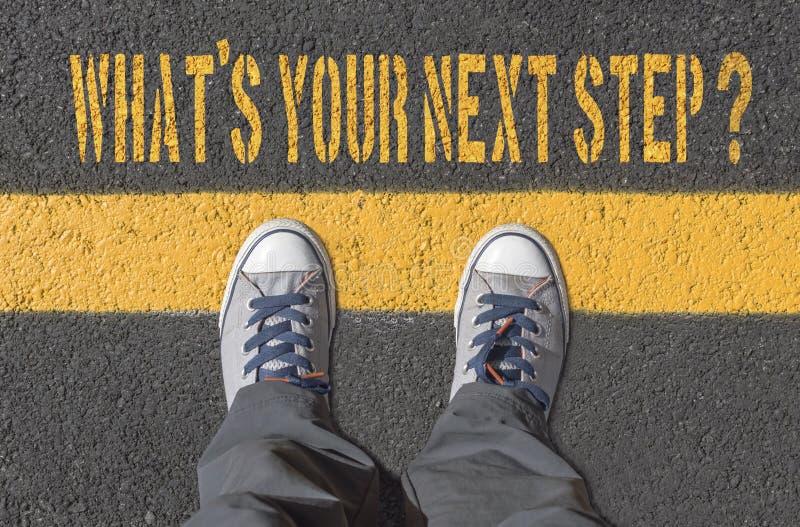 Vilken ` s ditt nästa steg? , tryck med gymnastikskor på asfaltvägen arkivfoton