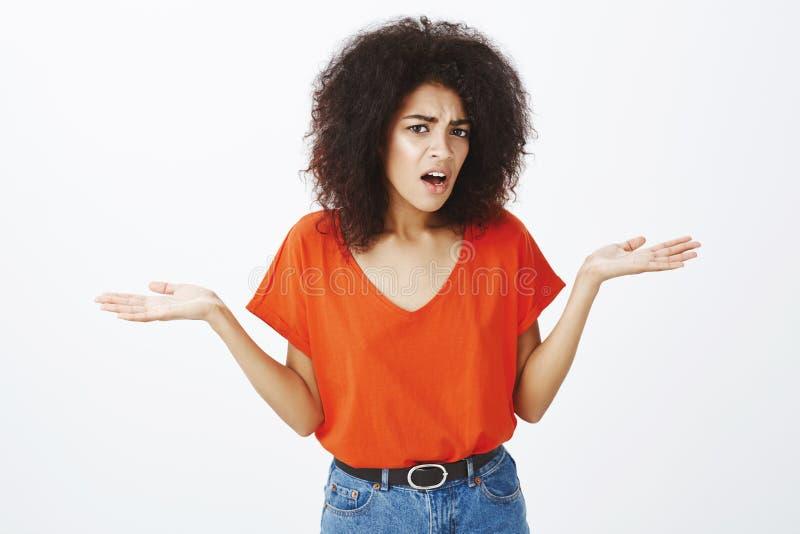 Vilket gå på Stående av den frustrerade ifrågasatte attraktiva mörkhyade kvinnlign med afro frisyr som rycker på axlarna royaltyfri bild
