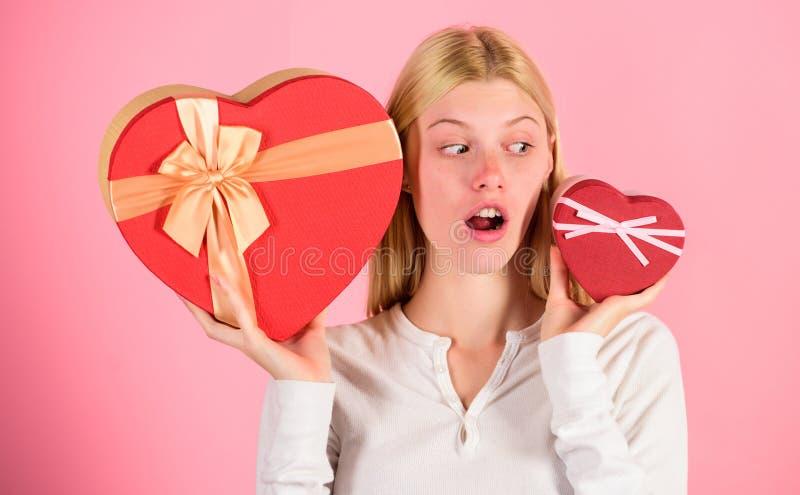 Vilket hon föredrar Flicka att avgöra vilken gåva hon gillar mer Stor överraskning och liten gåva Gör valet Romantisk gåva för arkivbild