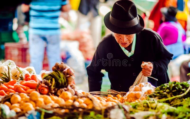 Villa de Leyva, Boyaca, Colombia - November 20th, 2014: Old indigenous woman buying fresh procucts on market stock images