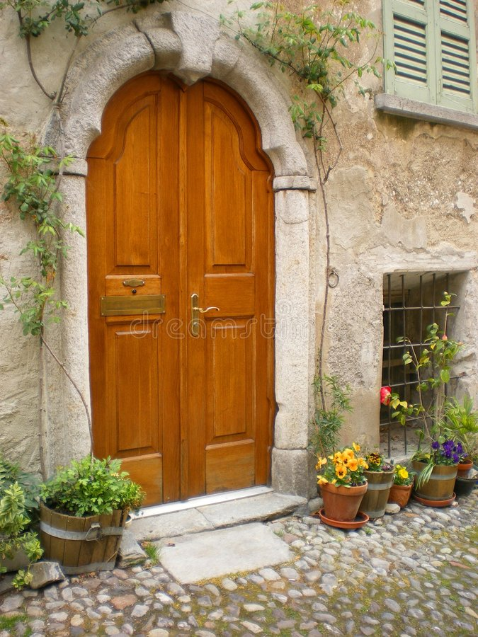 Villa Italy Tuscany arched door. Arched villa entrance door Tuscany Italy, arched-door in stone with cobbled village street and shuttered windows on an Italian stock photo
