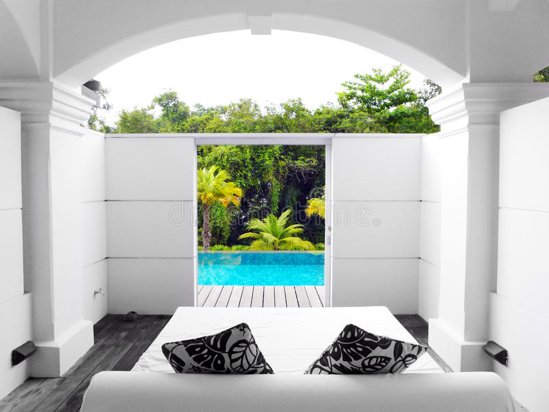 Villa luxurious with pool and garden view. A photograph showing the pretty swimming pool and tropical gardens view from the back yard and day bed of a luxury stock photos