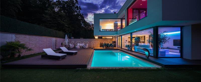 Villa moderna con le luci principali colorate alla notte immagine stock libera da diritti