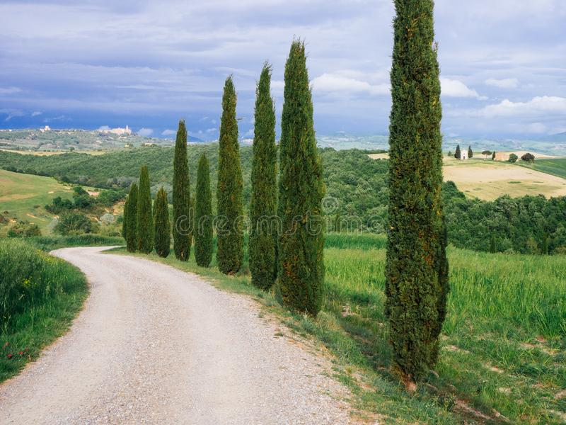 Villa in Tuscany with cypress road and blue sky, idyllic seasonal nature landscape vintage hipster background royalty free stock images