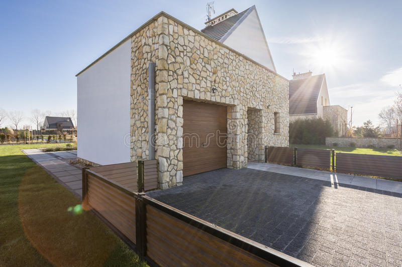 Villa with wood fence. Garage and stonework elevation royalty free stock images