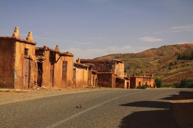 Village abandonné des maisons d'argile le long de route vide en montagnes d'atlas, Maroc photos stock