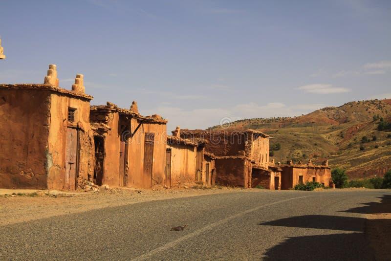 Village abandonné des maisons d'argile le long de route vide en montagnes d'atlas, Maroc image libre de droits
