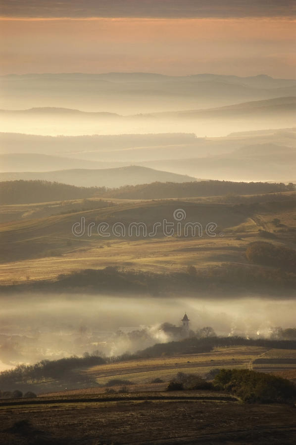 Village on autumn morning. Between hills with fog royalty free stock image
