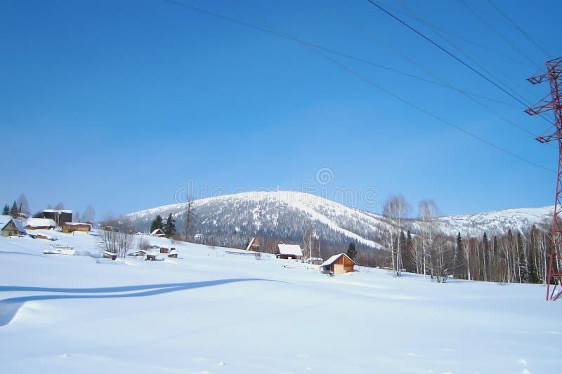 Village bloqué par la neige au pied de gamme de montagne images libres de droits