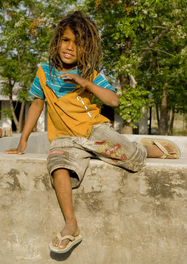 Download A Village Boy Sitting On A Small Wall Stock Image - Image: 24312007
