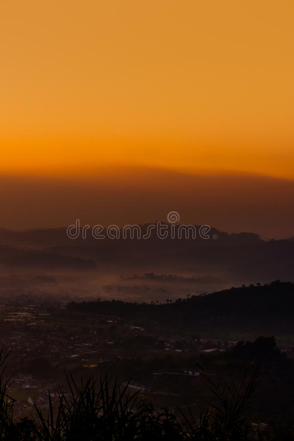 Village brumeux et montagne posée au lever de soleil photographie stock