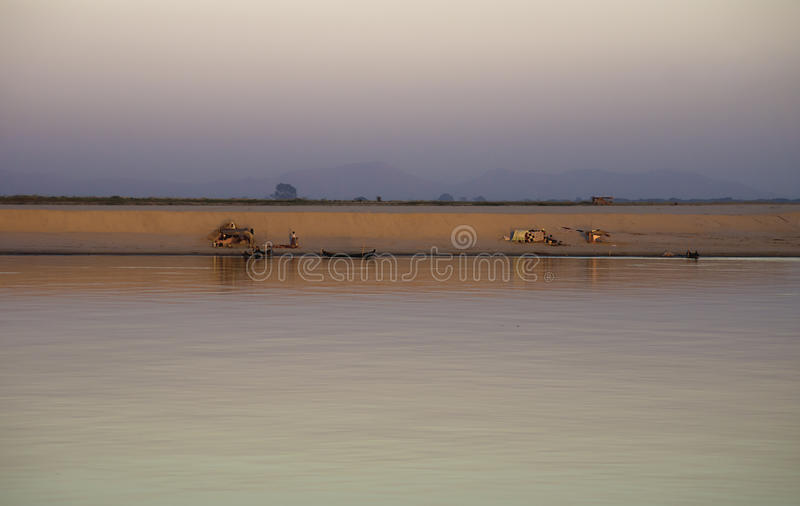 Village camp along the Irrawaddy during sunset. Sunset village scenery along the Irrawaddy river, Myanmar royalty free stock image