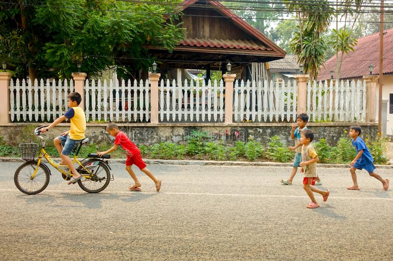 Village child driving a bicycle with friend help stock photography