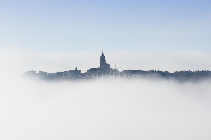 Village covered in fog with some houses and the church tower protruding above the clouds. Winter landscape. Thermal inversion. Sea of clouds. Spain, Huesca royalty free stock images