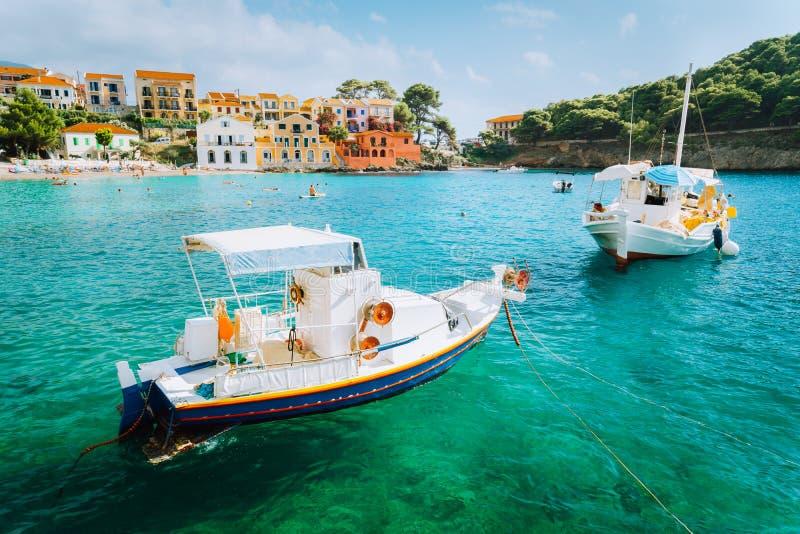 Village d'Assos sur l'île de Kefalonia, Grèce Les bateaux blancs dans l'émeraude ont ondulé la baie d'eau de mer image stock