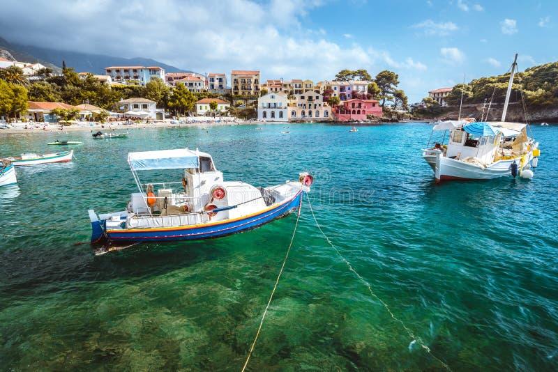 Village d'Assos sur l'île de Kefalonia, Grèce Les bateaux locaux bleus blancs à l'ancre dans l'émeraude ont ondulé la baie d'eau  image stock