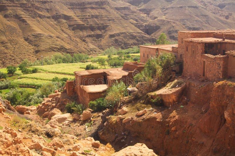 Village de Berber en vallée entourée par les murs rocailleux de haute montagne avec de vieilles maisons d'argile de brique photographie stock libre de droits