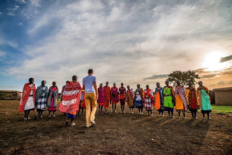 VILLAGE DE MAASAI, KENYA - 2 JANVIER 2015 : Personnes de touriste et de Maasai photo libre de droits