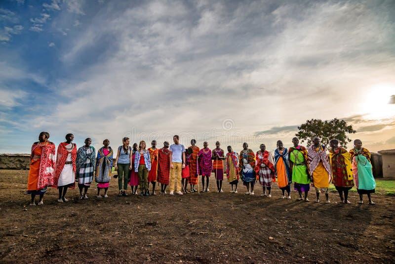 VILLAGE DE MAASAI, KENYA - 2 JANVIER 2015 : Personnes de touriste et de Maasai image stock