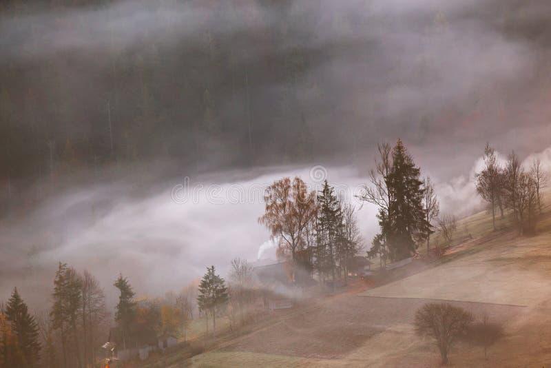 Village de montagne en nuages de brouillard et de fumée Matin d'automne image stock