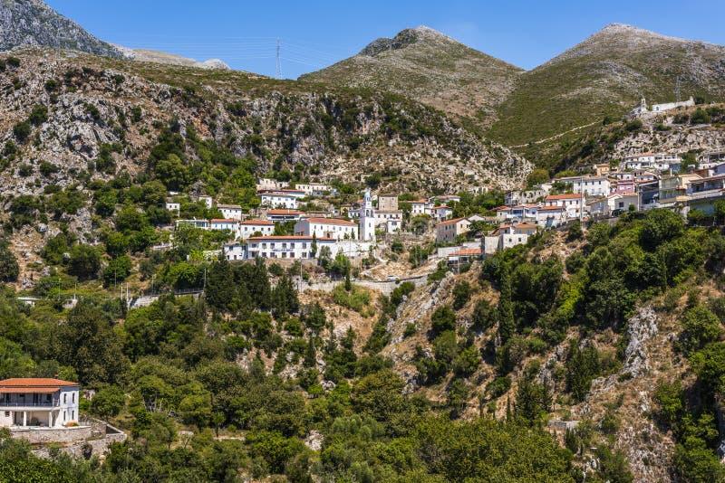 Village de montagne scénique de Dhermi avec le bâtiment scolaire dans l'église de ` de shkolla de ` de langue et les maisons alba image stock