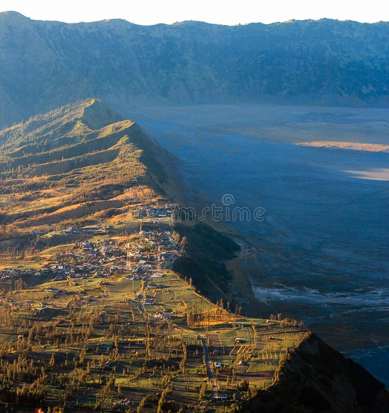 A village on the edge of Tengger Caldera. Farmlands and a village on the edge of Tengger Caldera, part of Bromo-Tengger-Semeru National Park in East Java royalty free stock image