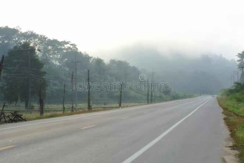 Village in the fog of winter at E-Tong Village, Kanchanaburi, Thailand. The road surrounded by forests has Thai kilometers written in (Sangkhlaburi and stock photography