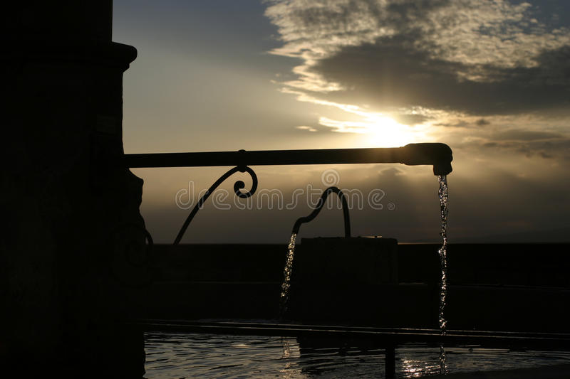 Village fountain at sunset in The Luberon, South eastern France. Ancient Water fountain in The Luberon in South West France. Rolling hills in the background. In royalty free stock photography