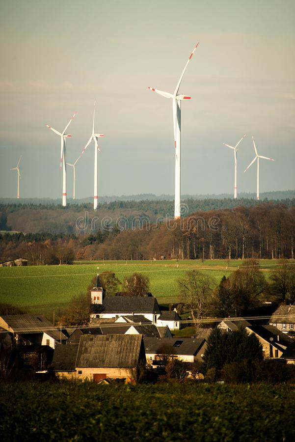 Village in front of panorama view over wind farm landscape in Germany with white generator turbines. Village in front of A panorama view over a wind farm royalty free stock photo