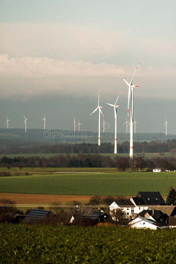 Village in front of panorama view over wind farm landscape in Germany with white generator turbines. Village in front of A panorama view over a wind farm stock images