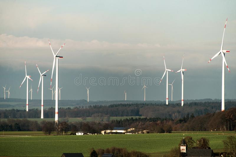Village in front of panorama view over wind farm landscape in Germany with white generator turbines. Village in front of A panorama view over a wind farm stock image