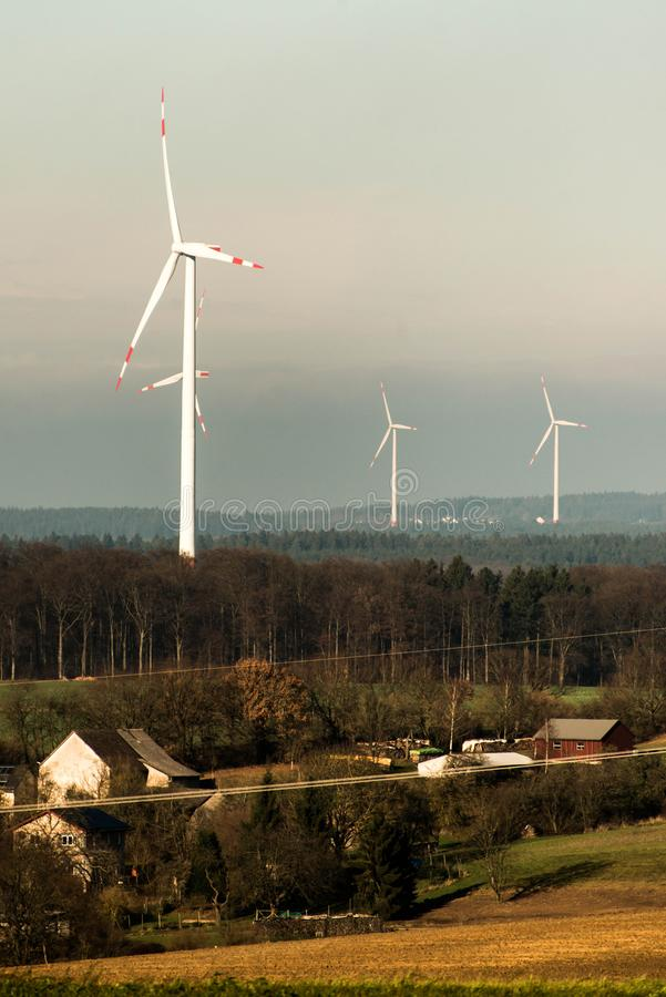 Village in front of panorama view over wind farm landscape in Germany with white generator turbines. Village in front of A panorama view over a wind farm stock photos