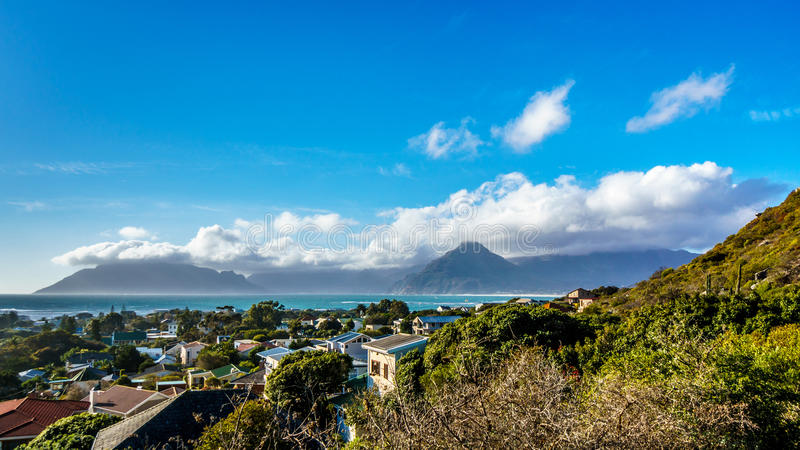 The village of Het Kommetjie with its famous kite-surfing beach in the Cape Peninsula. Of South Africa with Table Mountain in the background royalty free stock image