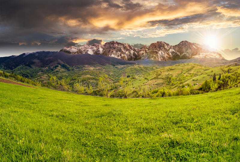 Village on hillside meadow in high mountains at sunset royalty free stock photos